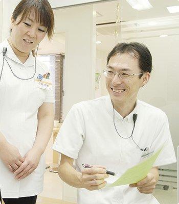 院長の深井統久と歯科衛生士の平岡利恵が患者様と話している写真